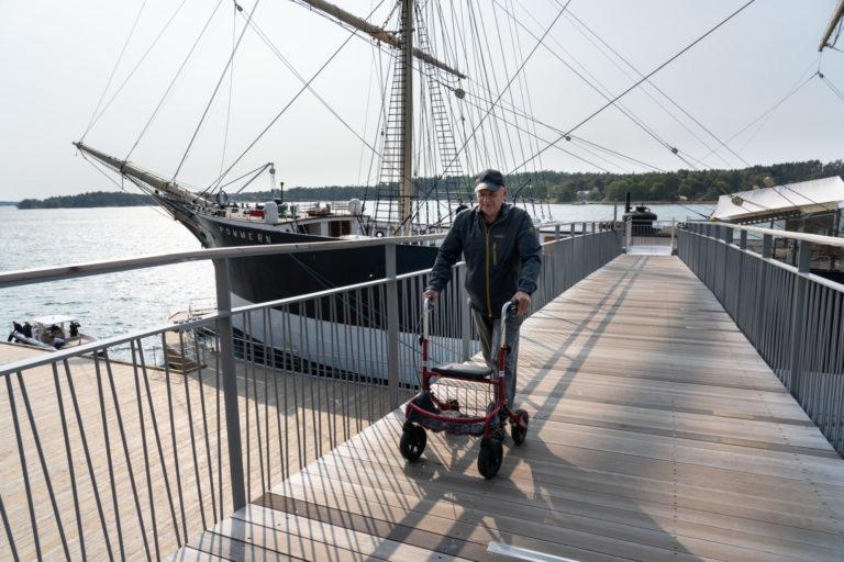 En äldre man syns framifrån. Han går över gångbron från Pommern mot land och håller i en röd rullator. Mannen är klädd i långbyxor, täckjacka och keps.