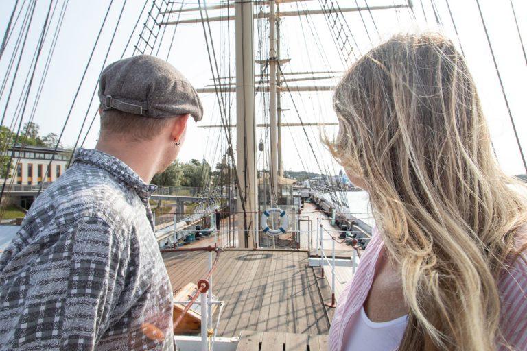 Man och kvinna tittar ut över segelfartyget Pommern.