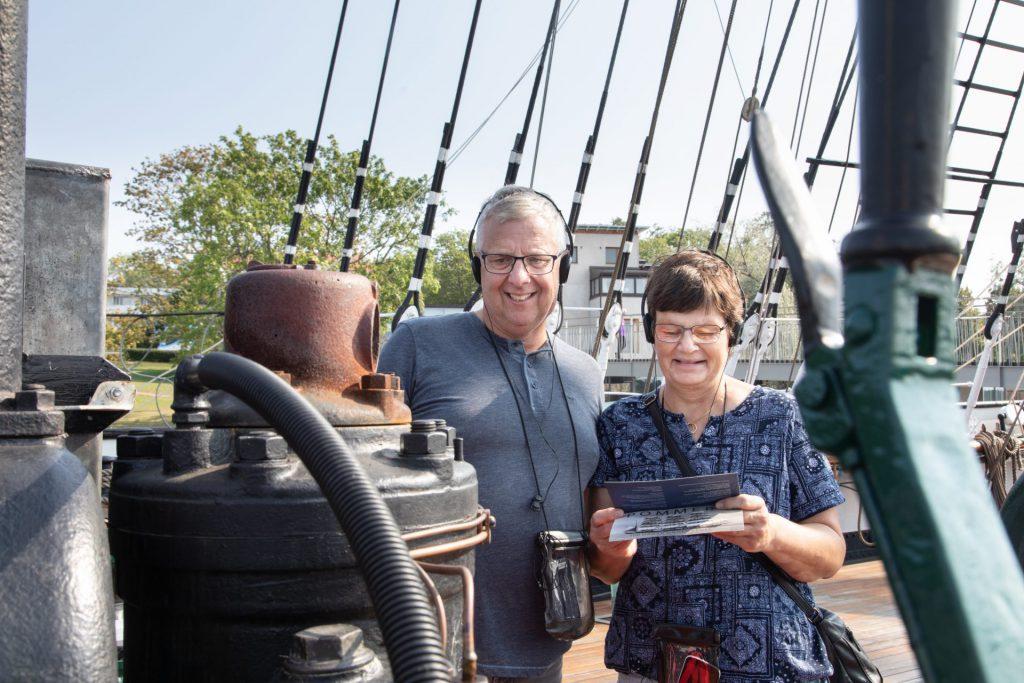 Man och kvinna tittar på kultändarmotorn ombord på segelfartyget Pommern.