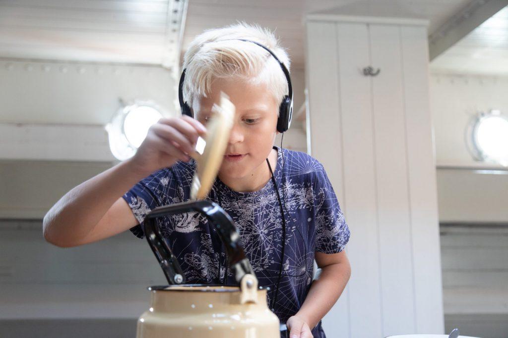 En pojke tittar ner i en kastrull ombord på segelfartyget Pommern.