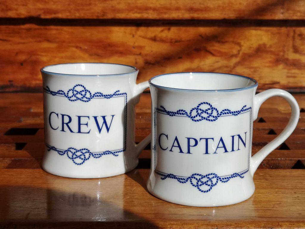 Muggar med texten crew och captain.